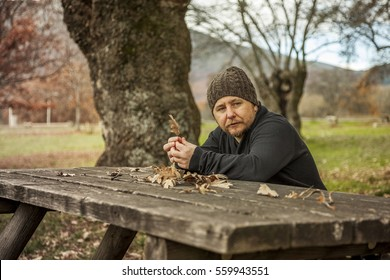 Man with wool hat sitting on the bench in the park in autumn background.