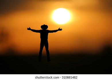 Man wore hat outstretched arms at   beautiful sunset.