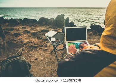 man at work in alternative office using laptop and smartphone to connect with internet and share things with the office. traveler concept digital nomad lifestyle all around the world