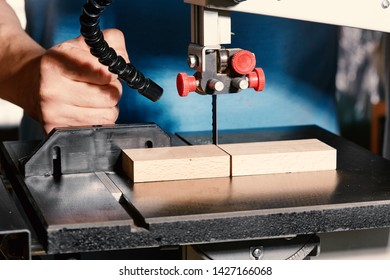 Man at work in the carpenter shop. The craftsman saws the workpiece on the bandsaw