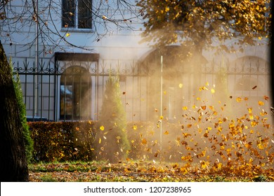man in work clothes blows off yellow and red fallen autumn leaves in Park, cleaning yard with wind turbine, cleaning lawn and footpaths on a Sunny day, colorful foliage blows the air flow and wind