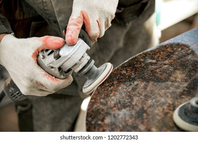 a man in work clothes and gloves polishes a marble stone with an angle grinder. grinding stone. manufacturing of monuments. marble slab. man with a tool