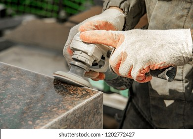 a man in work clothes and gloves polishes a marble stone with an angle grinder. grinding stone. manufacturing of monuments. marble slab
