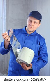 A man in work clothes holding a roll of foiled insulation for windows