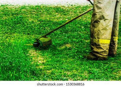man in work clothes mows green grass with trimmer
