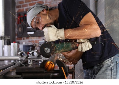 man work in home workshop garage cut metal pipe, goggles and construction gloves, cutting metal makes sparks closeup, diy and craft concept