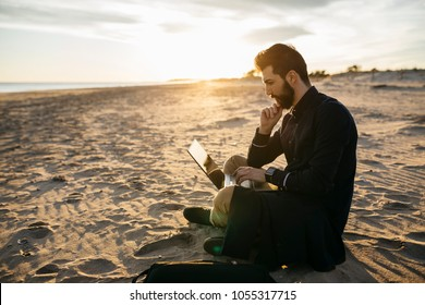 Man work on computer at the beach at sunset