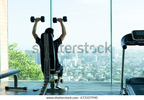 Man work out with dumbbells at the gym with city view