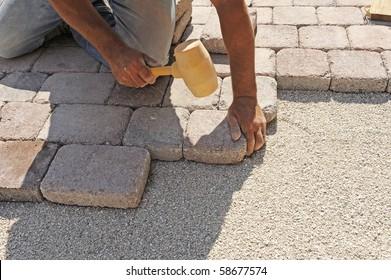 man at work paving stones with rectangular