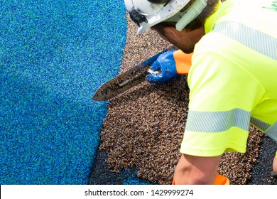 Man work at the side work. Construction side work. making a floor with the rubber beads on playground, New childrens playground under construction. Slide in the park playground. big plastic toy,