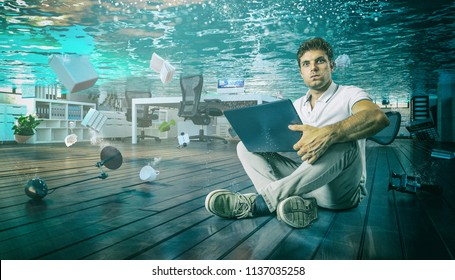 man work sit on the floor with his laptop in flooded office