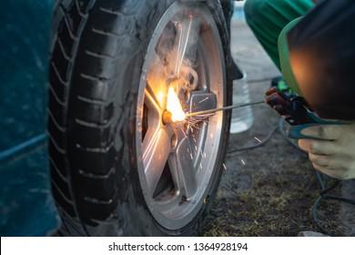 Man work with welding. Mechanical tools for auto service and car repair in Car repair shop and Worker repairing car.Car wheel repair