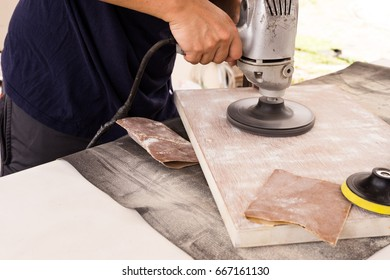 the man worker carpenter polishing a wooden board for painted