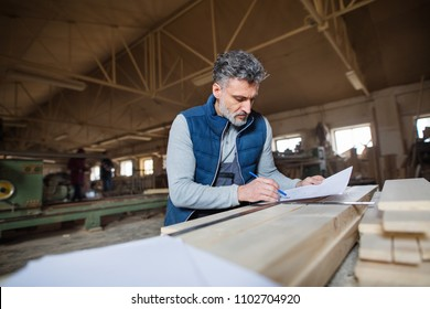 A man worker in the carpentry workshop, making plans.