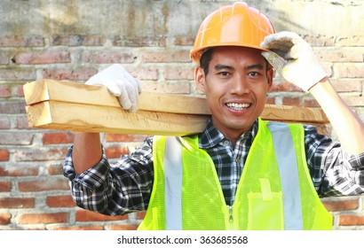 Ein Arbeiter, der Holz trägt und lächelt, sieht auf der Kamera mit einer Wand im Hintergrund