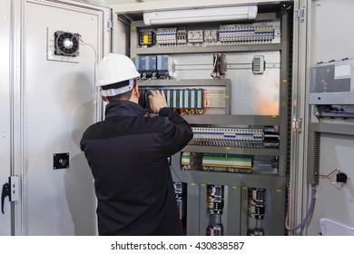 Man worker checking advanced industrial control panel