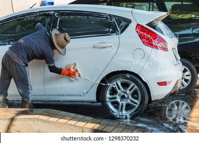 Man worker cleaning automobile with sponge on a car wash