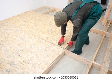 Man worker fits wooden oriented stands bords on insulated floor. New house constuction