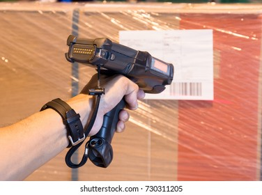 Man worker handling barcode scanner with scanning products in warehouse factory