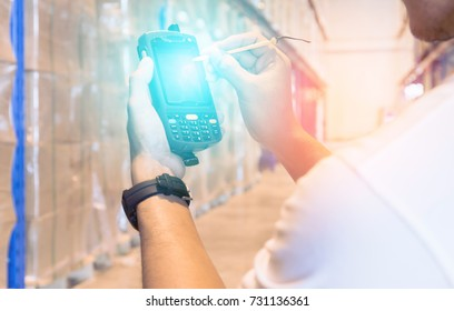 Man worker handling barcode scanner checking and manage a products in warehouse factory