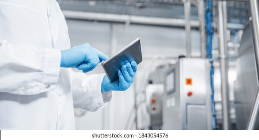Man worker holding tablet computer checking production line dairy factory food industry. Copy space banner.