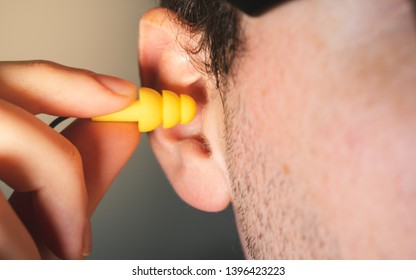 Man worker inserting yellow hearing safety protection earplug in his ear close-up view