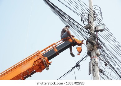 Man, worker on top of crane tractor for maintenance electric cables without safety belt is risk work. Concept of unsafe work place, risk work, unsafe work.