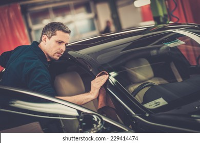 Man worker polishing car on a car wash