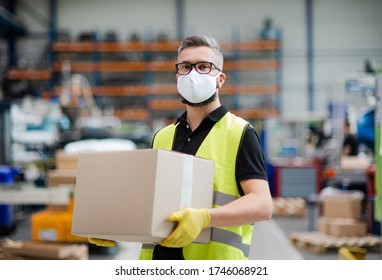 Man worker with protective mask working in industrial factory or warehouse.