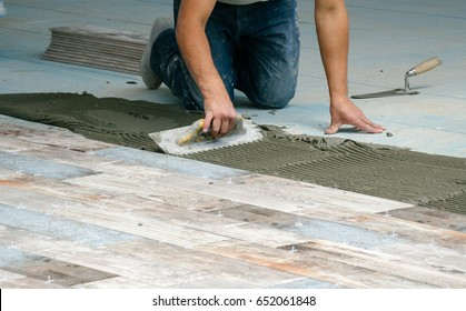 A man worker puts the tile using cement.