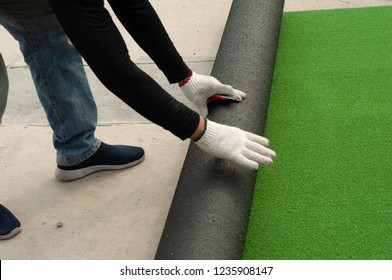 Man worker unroll roll of Artificial green grass turf outside. Artificial grass instalation