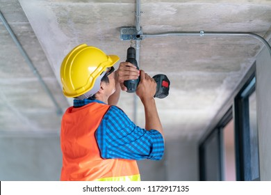 A man worker use electric drill screwdriver to fix in electric junction box in renovate home building
