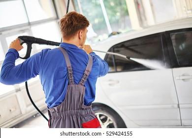 Man worker washing car on a car wash.
