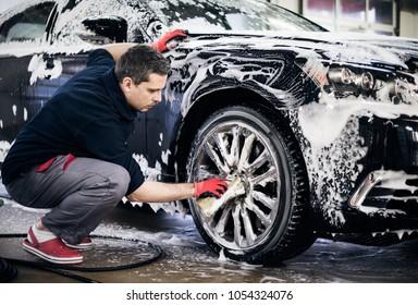 Man worker washing car's alloy wheels on a car wash.