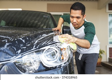 Man worker washing car's on a car wash. Cleaning concept.