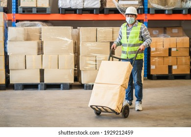 man worker wearing protective face mask and safety suite pushing cart with parcel box in factory warehouse, logistic industry concept.