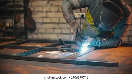 A man worker welding the seams between the metal beams indoors