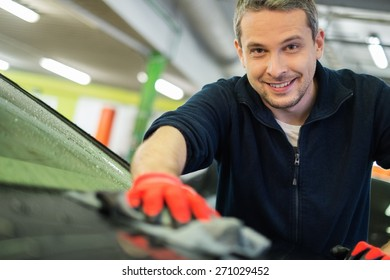 Man worker wiping car on a car wash