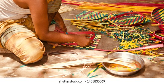 Man working with bamboo made objects sitting in a place