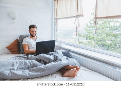 Man working in bed on laptop early in the morning