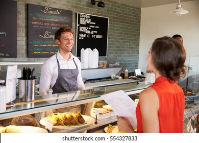 Man Working Behind Counter In Delicatessen Taking Food Order