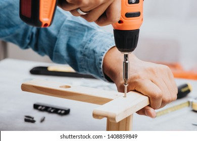 The man working with black-orange cordless screwdriver. Power tool for construction and DIY.