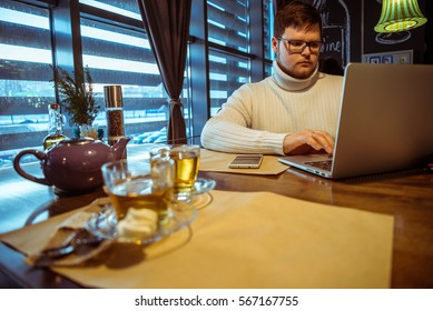 man working in cafe with laptop and cup of tea