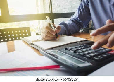 man working with a calculator and a document placed on a table.