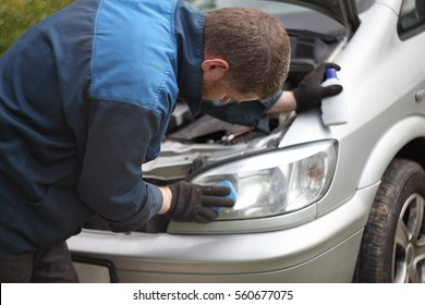 Man in working clothes holding a tools and polishing the front headlight of the car. Auto mechanic worker rubs element automobile. Concept for repair service station, work in the garage, car care.