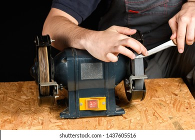 A man in working clothes hones professional sharpening kitchen knives