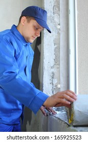 Man in working clothes places the foiled insulation on the window sill