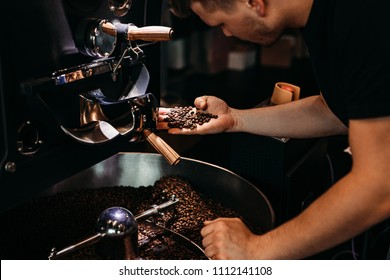 Man working at coffee production. Barista controling coffee grounds roasting process.