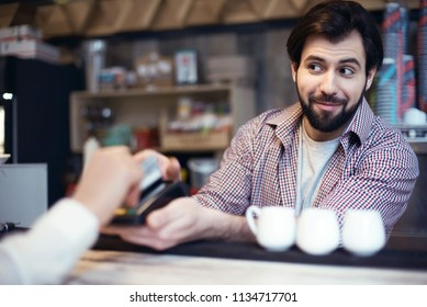Man working in a coffee shop taking cashless payment by credit card blurred smiling looking at customer
