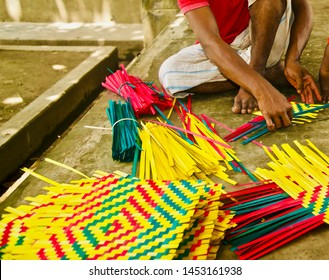 Man working with colourful bamboo objects sitting in a place